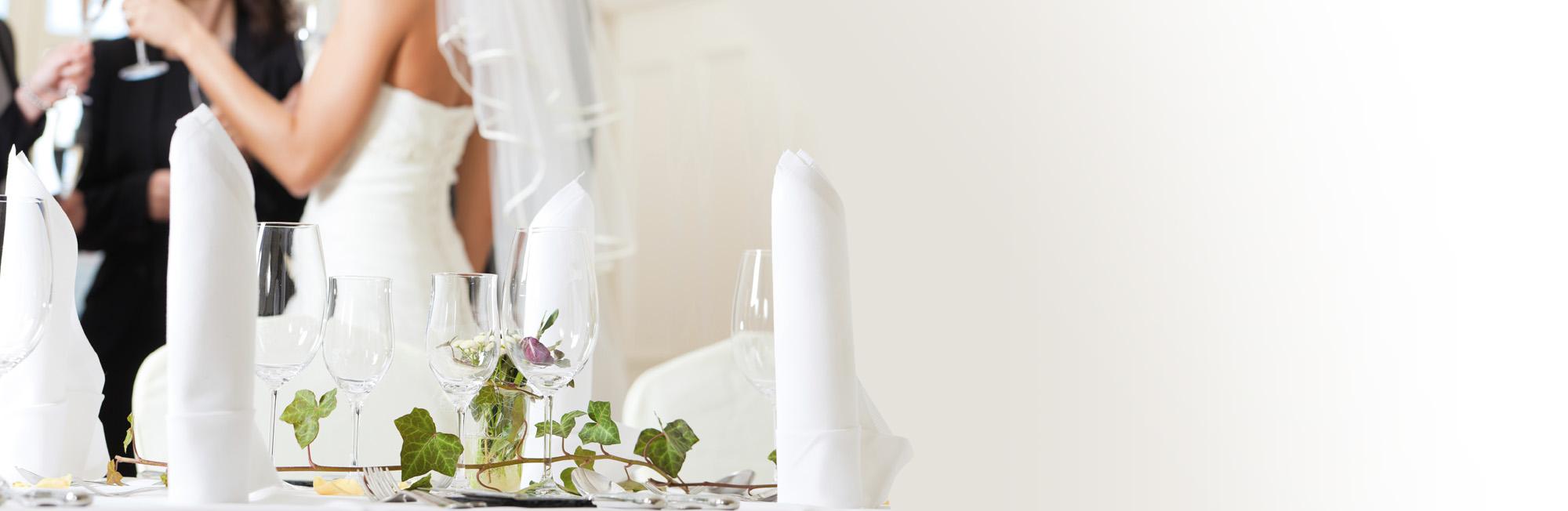 Une table de réception de mariage avec en fond de l'image les mariés